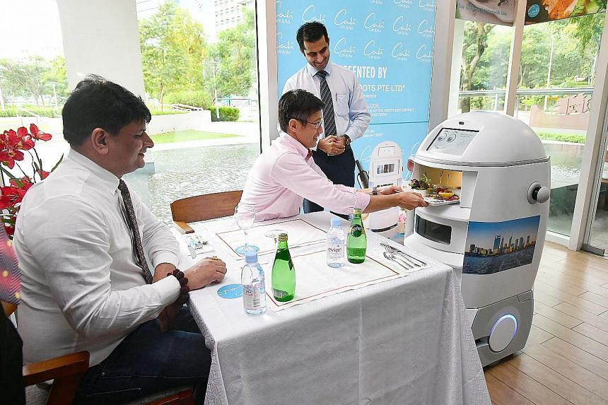 At the Park Avenue Rochester Hotel, Minister of State for Manpower Teo Ser Luck takes a dish out of a food service robot, developed by food and beverage solutions provider Happy Roots. With Mr Teo are the firm's founder and CEO Neelendra Jain (left),