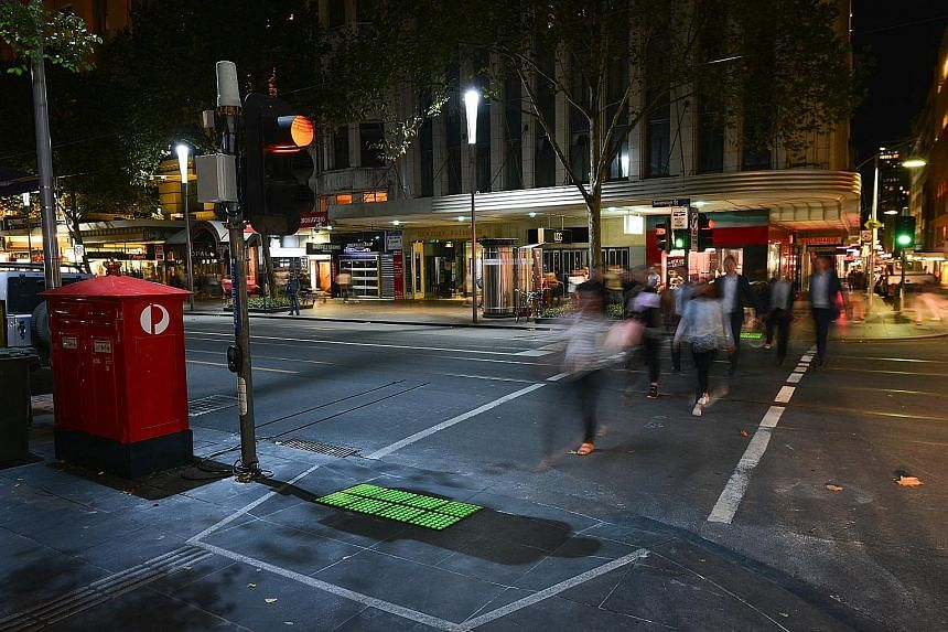 In-ground traffic lights at Melbourne's central business district. Green and red lights, which flash when the road signal is about to change, have been installed on the footpath at the intersection of Little Collins and Swanston streets.