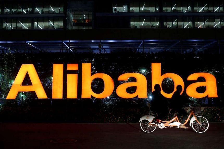 People riding a double bicycle past a logo of The Alibaba Group at the company's headquarters on Hangzhou, Zhejiang province.