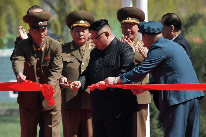 North Korea's leader Kim Jong-Un (centre) cutting the red ribbon at a ceremony for the opening of a housing project in Pyongyang on April 13, 2017.