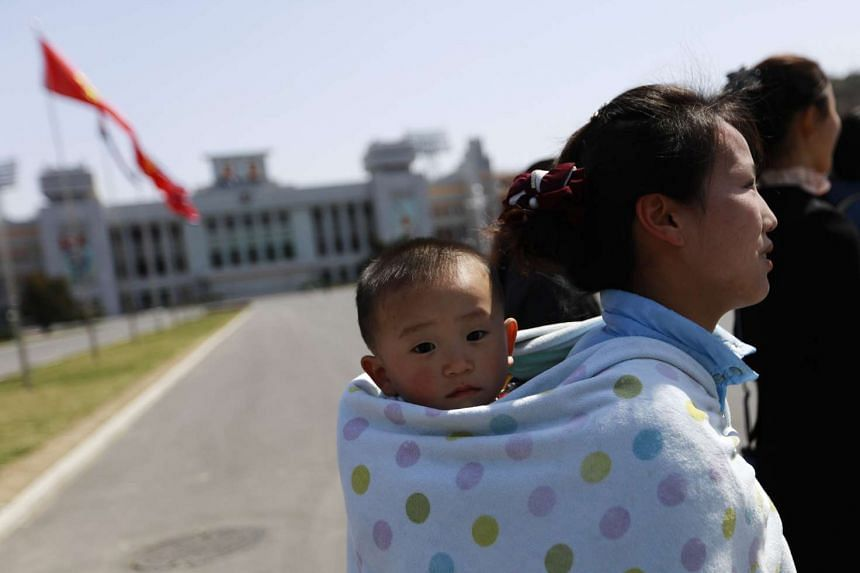 A woman with her baby outside the Kim Il Sung Stadium in Pyongyang.