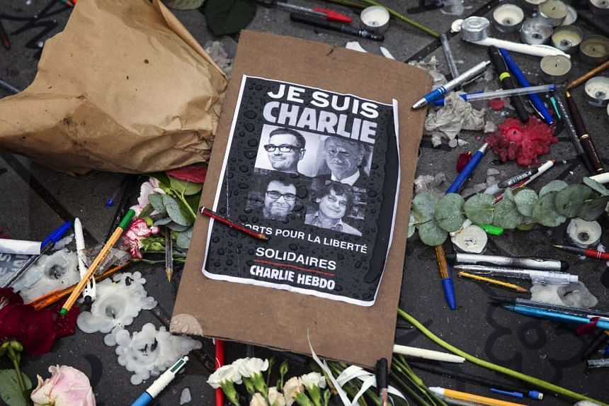 """A poster reads """"Je suis Charlie"""" (I am Charlie) amid symbolic pens and pencils in 2015, commemorating those killed in a shooting at French satirical magazine Charlie Hebdo."""