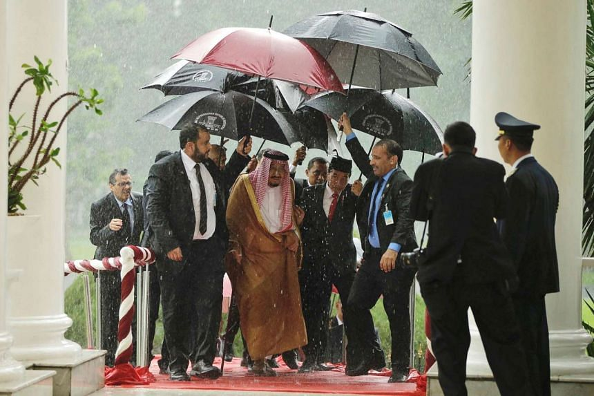 Saudi Arabia's King Salman and Indonesian President Joko Widodo walk under umbrellas in heavy rain during their meeting at the Presidential Palace in Bogor, West Java, Indonesia, on March 1, 2017.