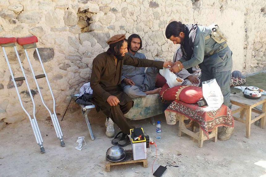 An Afghan medic treats a policeman wounded in a military operation against suspected ISIS militants in Achin, April 14, 2017.