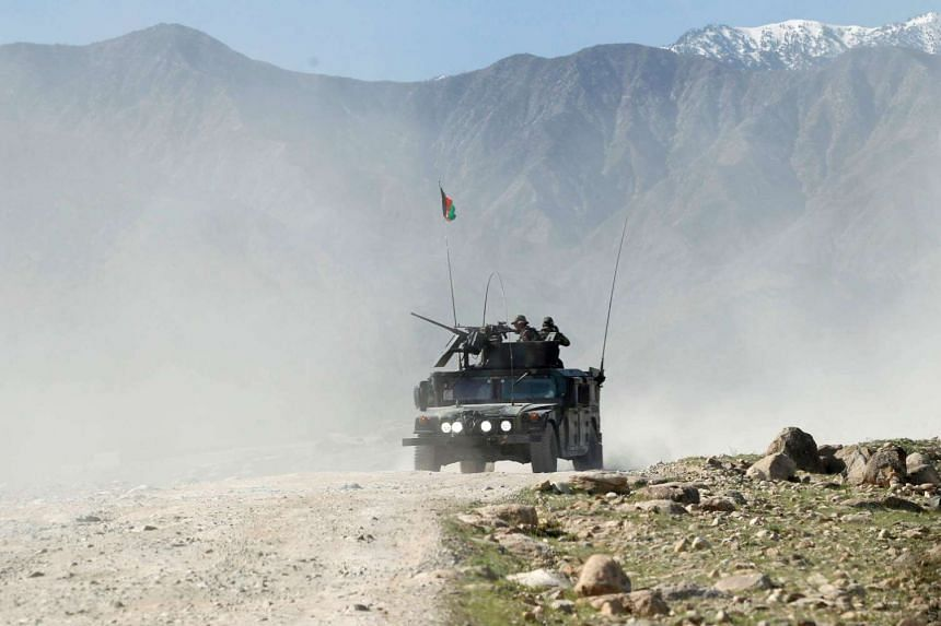 Afghan special forces patrol in Pandola village near the site of a US bombing in Achin.