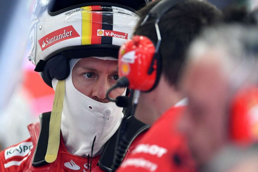 Ferrari's German driver Sebastian Vettel talks to one of his engineers during a practice session ahead of the Bahrain Grand Prix.