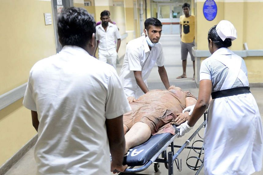 Sri Lankan hospital workers bring in a wounded woman to the main hospital in Colombo.