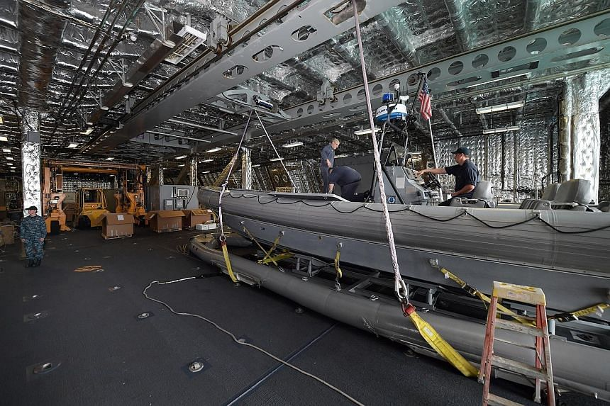 A rigid-hulled inflatable boat in the large mission bay of the USS Coronado, which can be easily configured for different operations. The Harpoon missile launchers (above) on the USS Coronado (right) at Changi Naval Base on Wednesday. Last July, the