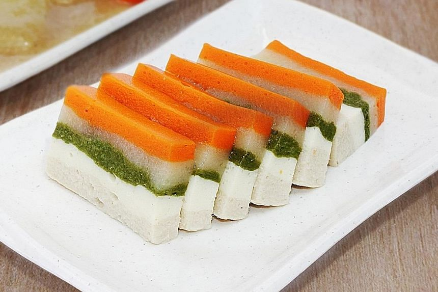 Coarsely minced seafood otak is among the ready-to-eat texture-modified Asian food created for those with swallowing difficulties. Multi-layered dish consisting of chicken, steamed egg, spinach, potato and carrot. Madam Chan Chin Chia having porridge
