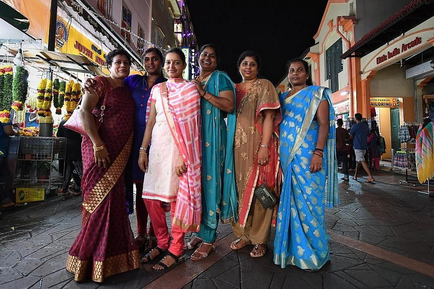 Madam Mohan Sumathy (fourth from left) with her family members in Campbell Lane last night. The family ended their New Year's Day watching a display of fireworks. Madam Sumathy's family had risen at 6am to decorate the entrance of their home, pray an
