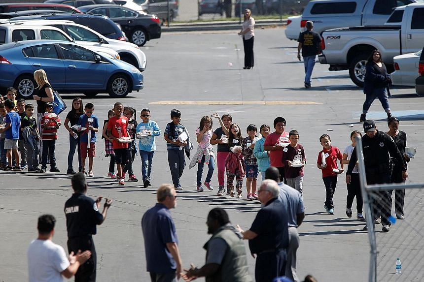 Pupils who were evacuated after a school shooting in San Bernardino, California, walking past well-wishers to be reunited with their waiting parents on Monday. A teacher and a pupil died when the teacher's estranged husband walked into their class an