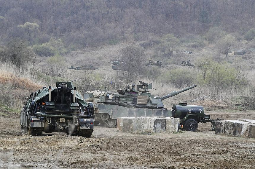 US Army soldiers with M1A2 tanks participating in a defence exercise conducted to simulate a response to an attack from North Korea, at a drill field in Gyeonggi province, South Korea, yesterday.