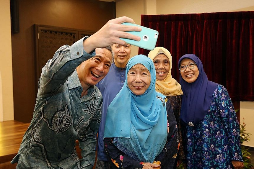 Prime Minister Lee Hsien Loong taking a wefie with Puan Noor Aishah, widow of President Yusof Ishak, and the Yusofs' children (from left) Imran Yusof, Orchid Kamariah and Zuriana Yusof at the Yusof Ishak Mosque yesterday. Above: Worshippers at the pr