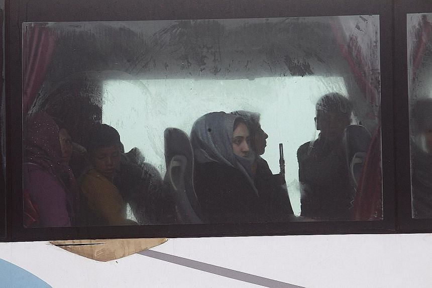 Evacuees from Kafraya and Fuaa on a bus at insurgent-held al-Rashideen, Aleppo province, yesterday. The exercise, due to start on April 4, had been delayed four times.