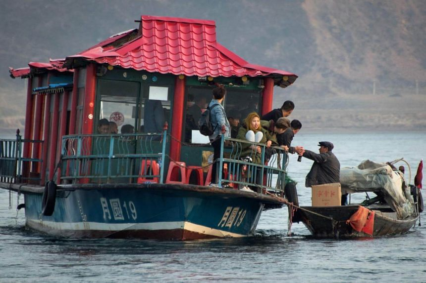 A man sells North Korean products to Chinese tourists from a boat on the river.