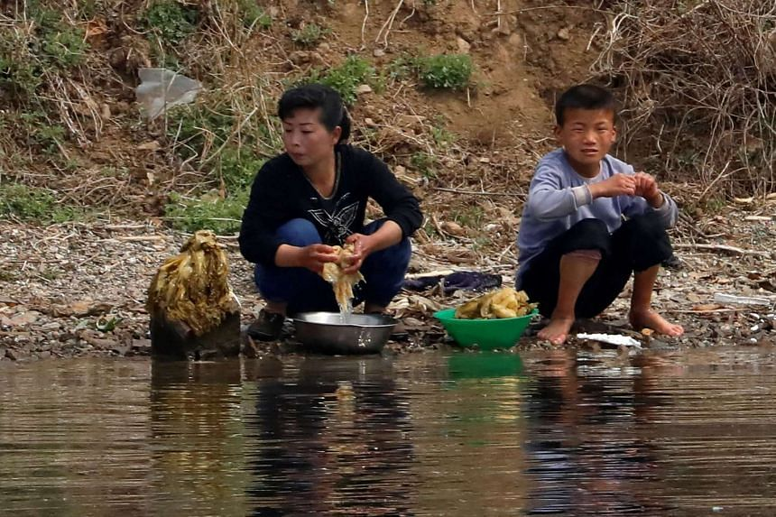 North Koreans washing vegetables in the river.