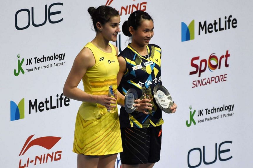 Tai Tzu-Ying of Taiwan (right) poses on the podium with second-placed Carolina Marin of Spain after their women's singles final of the Singapore Open badminton tournament.