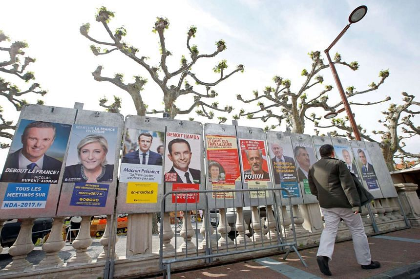 A man walks past campaign posters of the 11 candidates who are running in the presidential election.