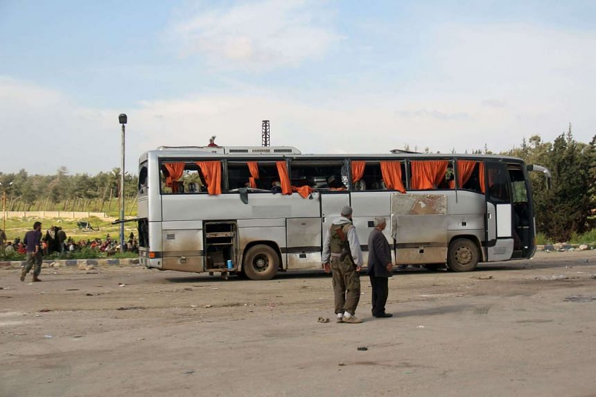 Rebel fighters standing next to a damaged bus following a bombing outside Aleppo that targeted buses carrying Syrian civilians.