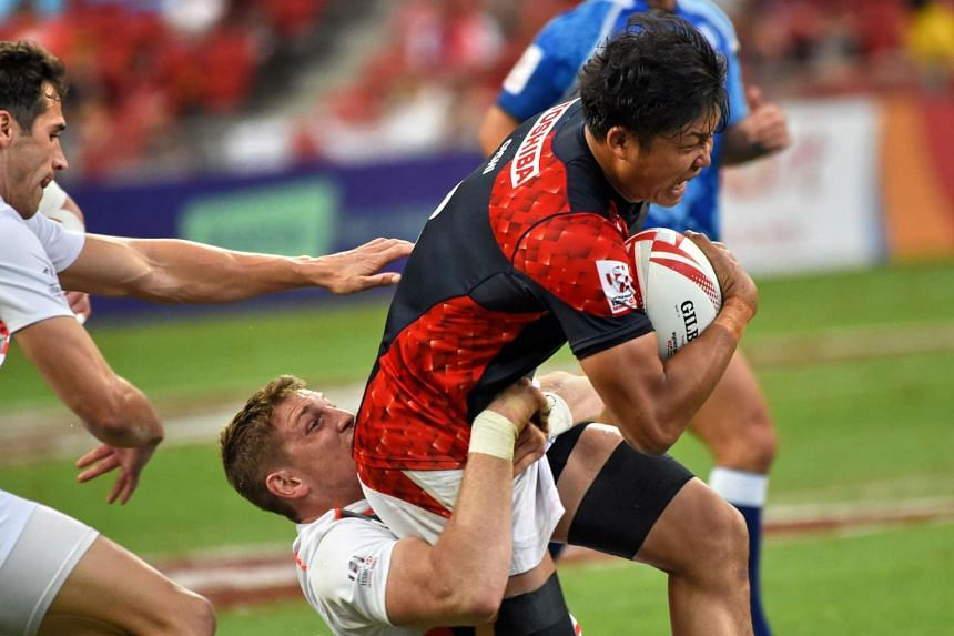 Rikia Oishi of Japan (right) competes for the ball with the England team during day one of the Singapore Rugby Sevens.