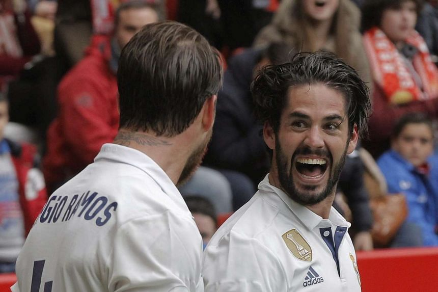 Real Madrid's midfielder Isco Alarcon (right) celebrates with his teammate Sergio Ramos (L) after scoring his team's third goal.