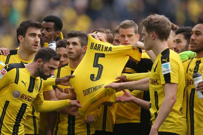 Dortmund's players hold the jersey of Dortmund's Spanish defender Marc Bartra who was injured during the bus attack.