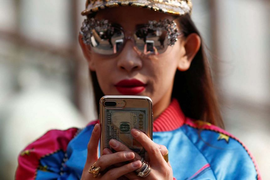 A file picture of a woman using her phone in Beijing. Auspicious phone numbers can go for thousands or even tens of thousands in China.