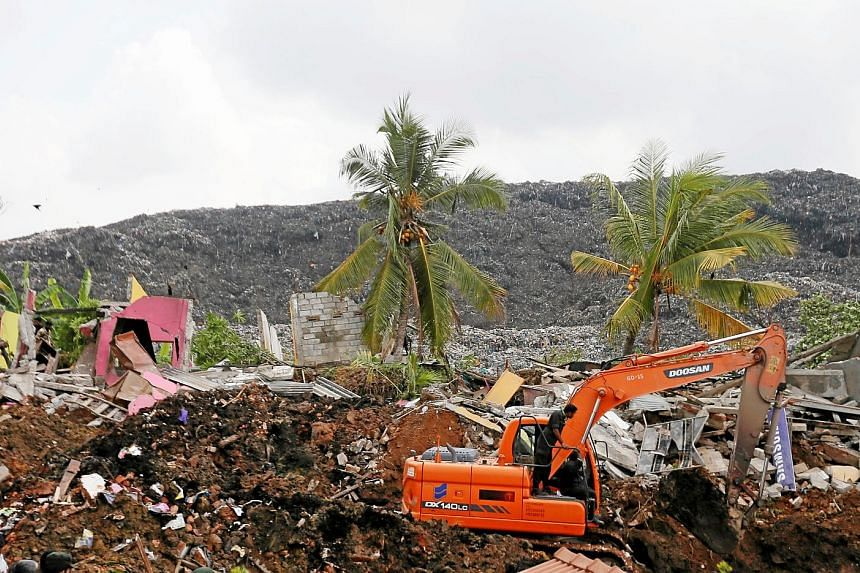 Soldiers use an excavator to dig through tonnes of rubbish to look for victims after a 91m-high garbage dump crashed on homes in Kolonnawa, Colombo, on Friday, leaving 19 people dead. The authorities said the death toll would have been much higher ha