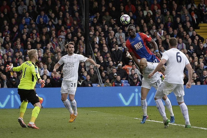 Crystal Palace striker Christian Benteke climbs over Leicester defender Yohan Benalouane in the 70th minute to head the equaliser past goalkeeper Kasper Schmeichel.