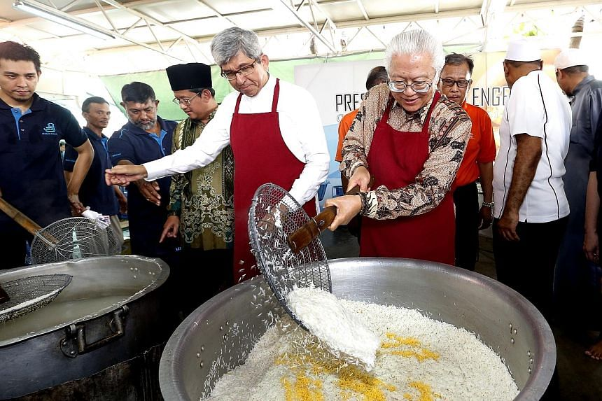 Minister-in-charge of Muslim Affairs Yaacob Ibrahim helping President Tony Tan Keng Yam add finishing touches to a pot of briyani at the President's Challenge Charity Briyani, his last one as President.