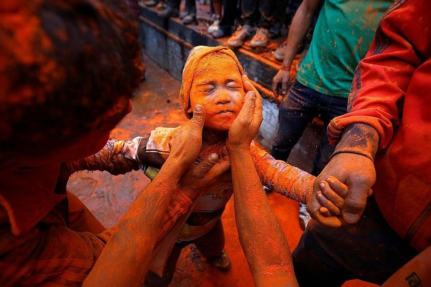 Spring has arrived and festivities are the order of the day as people prepare to celebrate its coming in Nepal. This boy getting his face smeared with vermilion powder yesterday during the Sindoor Jatra festival in the ancient city of Thimi, on the o