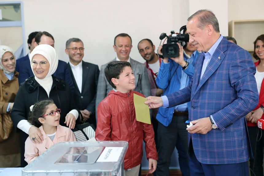 Turkish President Recep Tayyip Erdogan (right) cast his vote with his grandson Mehmet Akif as his wife Emine and granddaughter Mahinur acompany him at a polling station for a referendum on the constitutional reform in Istanbul on April16, 2017.