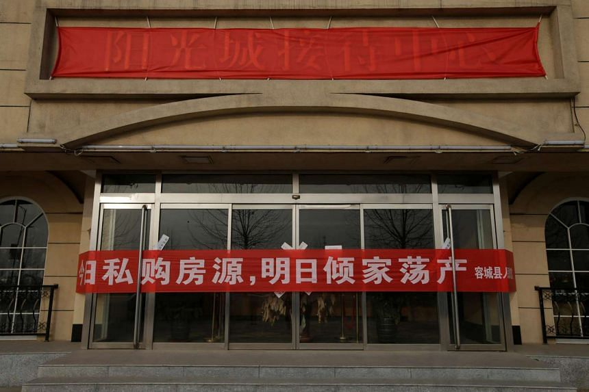 A banner warning illegal property purchase is placed on the gates of a closed sales office of a property after the government banned new property sales in counties earmarked as part of a new special economic zone in Rongcheng county, Hebei province,