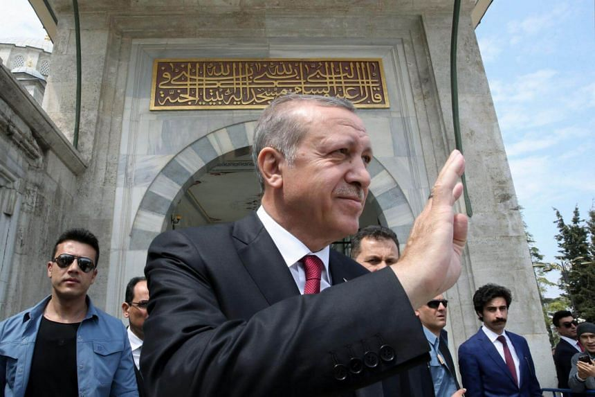 Turkish President Recep Tayyip Erdogan (centre) greeting his supporters during a visit to the Ottoman Fatih Sultan Mehmet's tomb in Istanbul, a day after his victory in a national referendum.