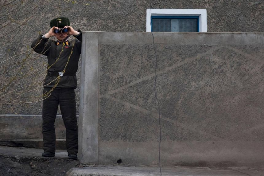 A North Korean soldier uses his binoculars on the banks of the Yalu river near Sinuiju, opposite the Chinese border city of Dandong on April 14, 2017.