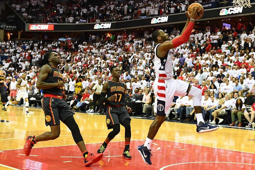 Washington Wizards guard John Wall (2) shoots a layup as Atlanta Hawks' Taurean Prince (12) and Dennis Schroder (17) look on during the fourth quarter in game one of the first round of the 2017 NBA Playoffs.