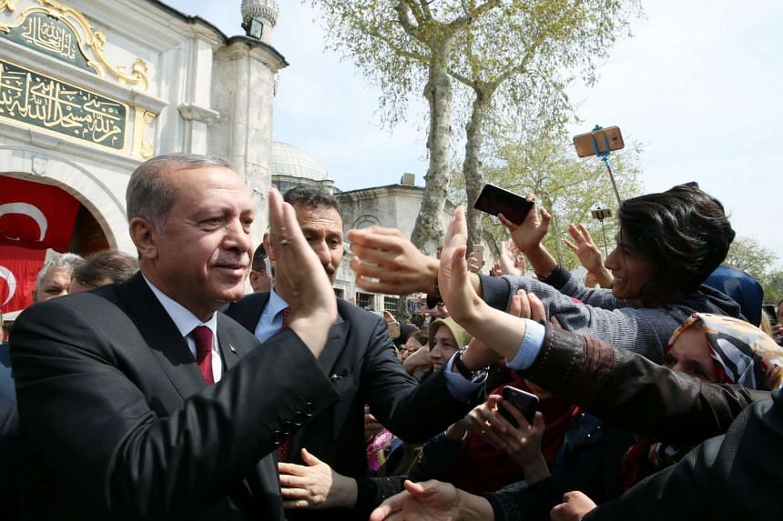 A handout photo made available by Turkish President Press office shows Turkish President Recep Tayyip Erdogan (left) greeting people after praying at Eyup Sultan mosque, Istanbul, Turkey, on April 17, 2017.