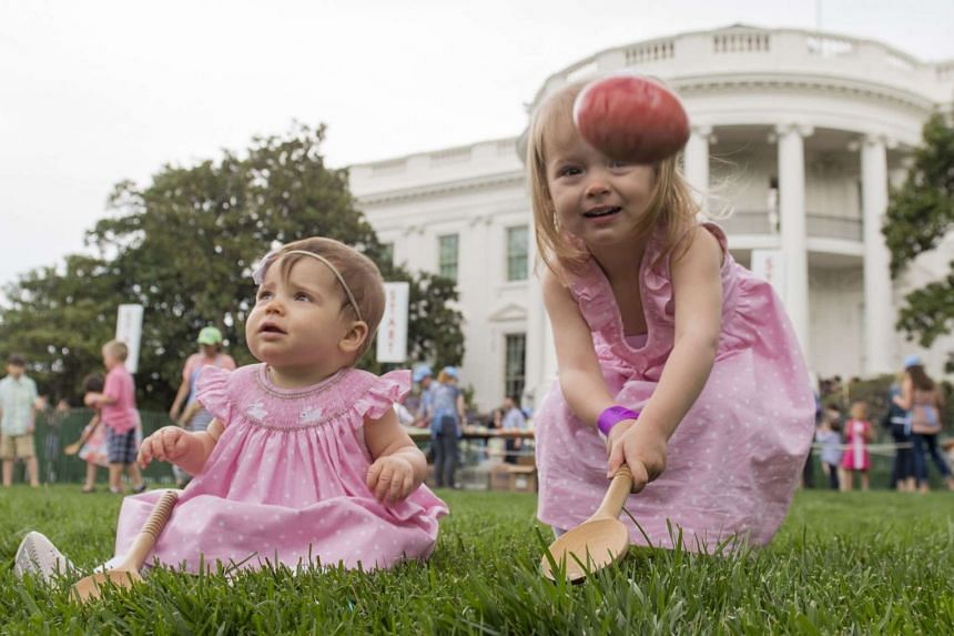 Three-year-old Abigail (right) and 10-month-old Caroline (left) participate in an Easter egg roll race during the 139th White House Easter Egg Roll on the South Lawn of the White House in Washington, DC on April 17, 2017.