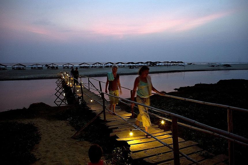 Western tourists at Mandrem Beach in Goa, which lures millions of tourists yearly with its nightlife and sandy beaches.