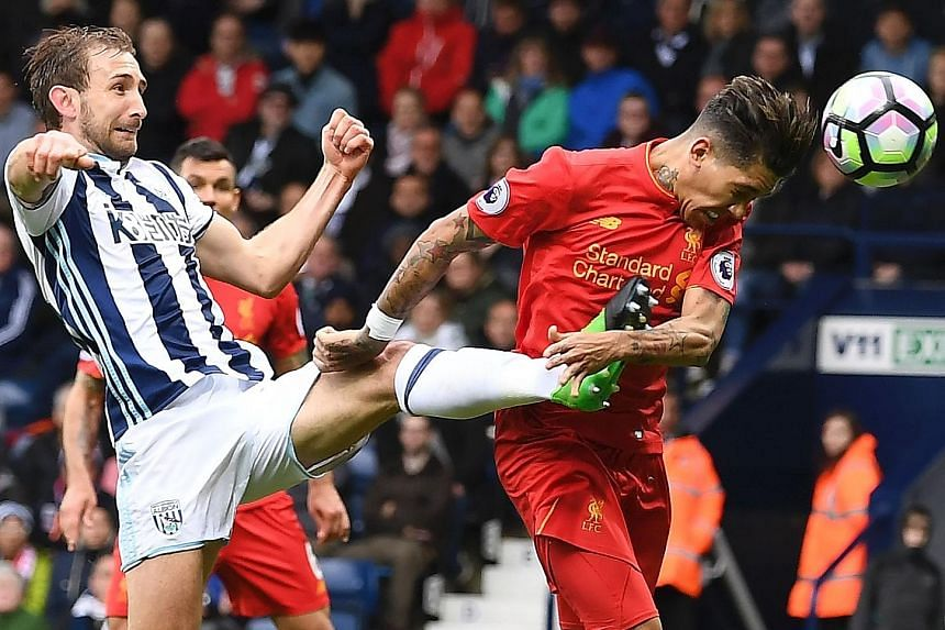 Liverpool midfielder Roberto Firmino beating West Brom defender Craig Dawson to head home a free kick for the only goal at The Hawthorns. The third-placed Reds have 66 points, two more than City.