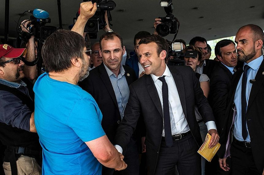 Mr Emmanuel Macron, smiling and unfazed, shaking hands with a supporter of rival candidate Jean-Luc Melenchon. French National Front leader Marine Le Pen about to be hugged by one of her supporters during an election campaign rally in Perpignan on Sa