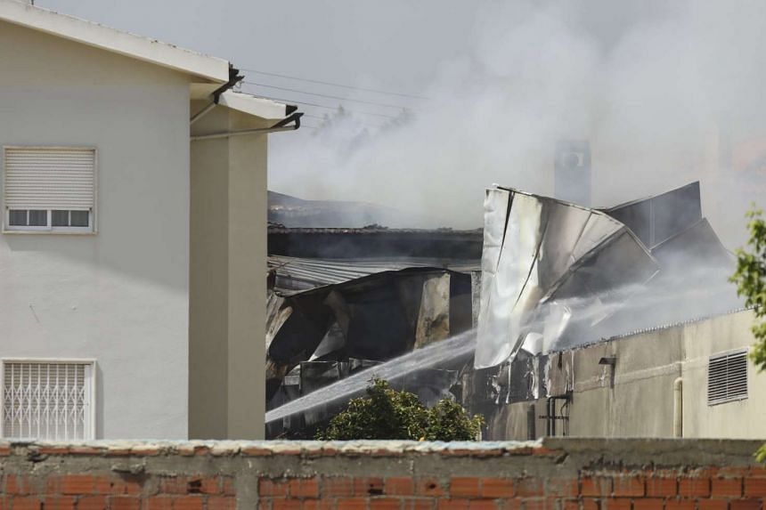 Smoke rising from buildings after a small airplane crashed into a supermarket carpark in Tires on the outskirts of Lisbon, Portugal, on April 17, 2017.