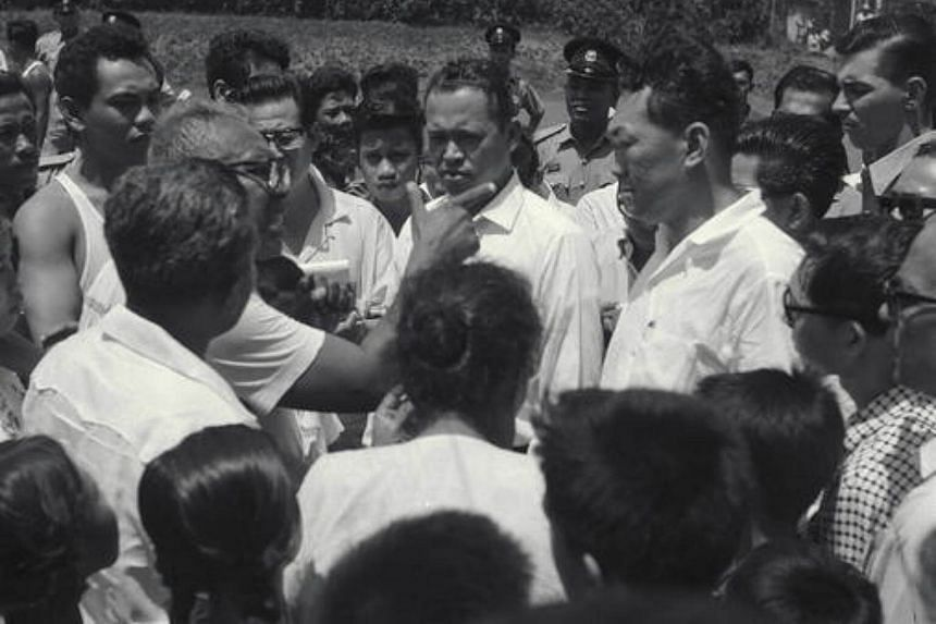 Then Prime Minister Lee Kuan Yew, accompanied by Mr Othman, tours troubled areas to meet community leaders during the racial riots of 1964.