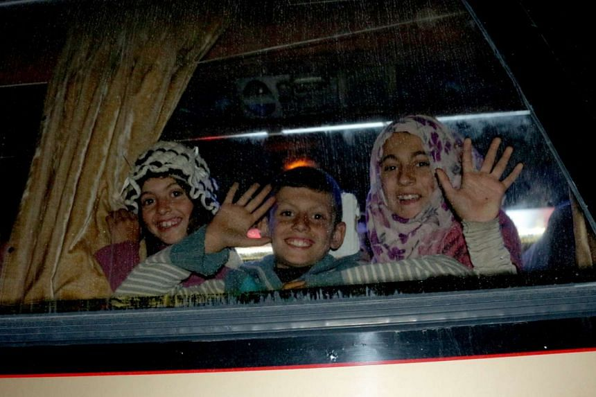 Syrian families wave from the window of bus after being evacuated from two besieged towns in Aleppo.