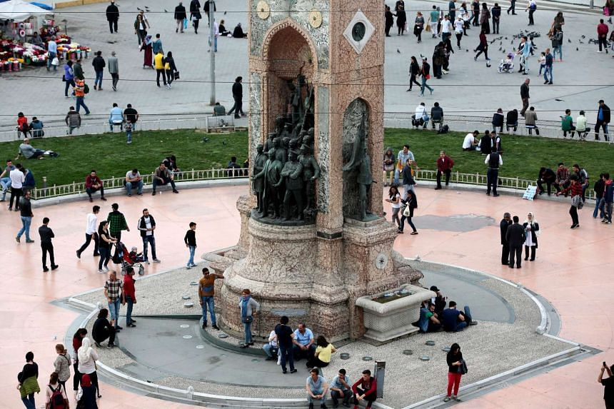 People make their way around the Republic Monument on Taksim Square in Istanbul on referendum day.