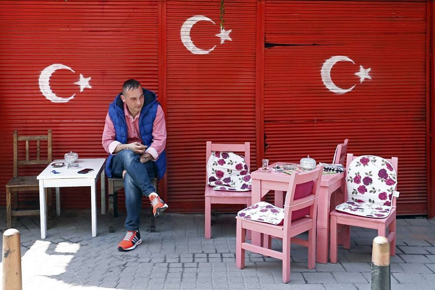 A man sits in a cafe decorated with Turkish flags near a polling station for the referendum in Istanbul.