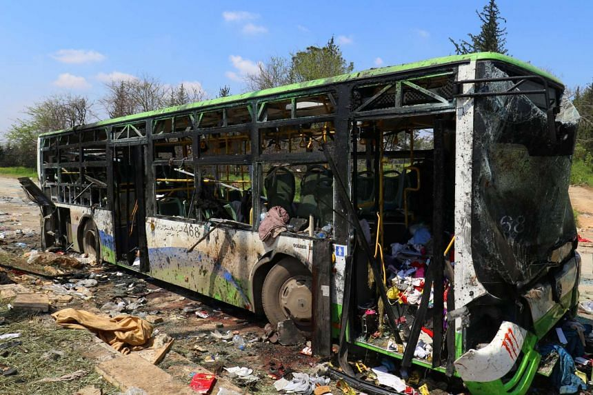 A damaged bus is seen on April 16, 2017 after an explosion at insurgent-held al-Rashideen in Syria's Aleppo province.