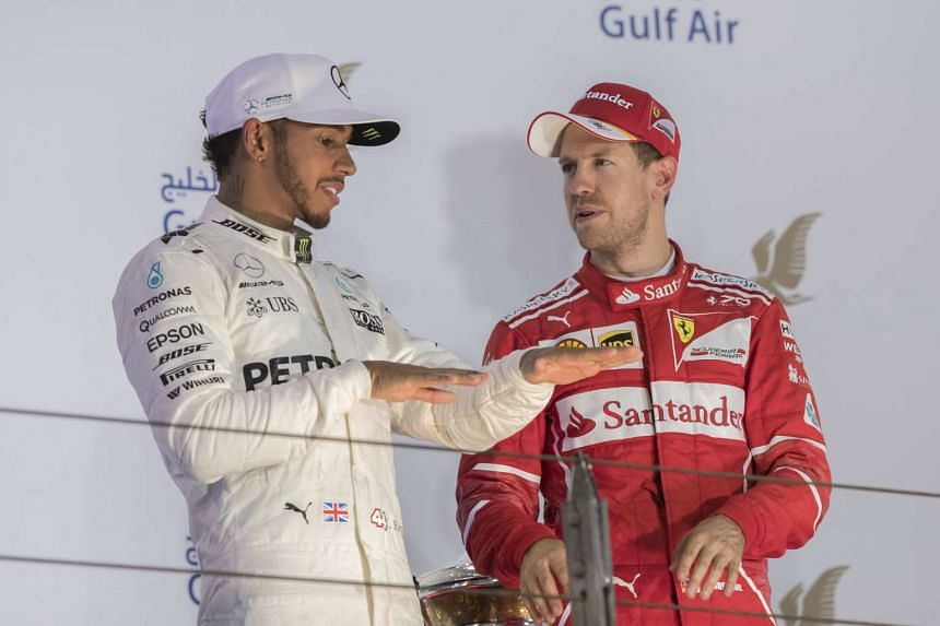 Sebastian Vettel (right) and Lewis Hamilton (left) chat on the podium after the Bahrain Formula One Grand Prix on April 16, 2017.