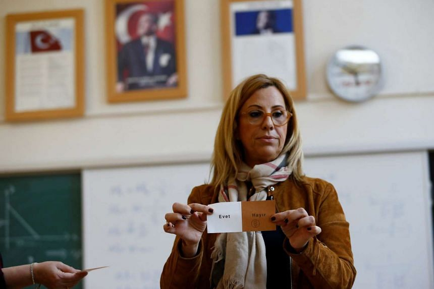 An election official displays a vote as they count at a polling station in Izmir, Turkey on April 16, 2017.