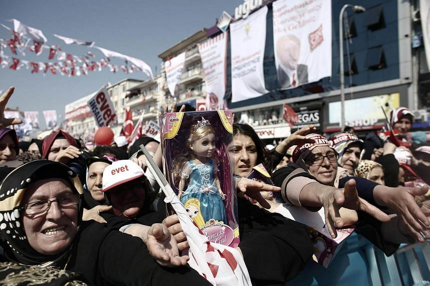 Attendees try to catch gifts such as dolls, thrown to them by Recep Tayyip Erdogan, Turkey's president (not pictured) during a Yes referendum campaign rally in Umraniye, Istanbul, Turkey, on April 15, 2017.